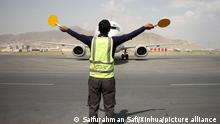 (210920) -- KABUL, Sept. 20, 2021 (Xinhua) -- A member of the ground crew gives signals to the pilot of a plane at Kabul International Airport in Kabul, capital of Afghanistan, Sept. 20, 2021. Efforts are underway to solve all technical difficulties before international commercial flights resume in Kabul International Airport, airport director Abdul Hadi Hamadani said on Monday. (Photo by Saifurahman Safi/Xinhua)