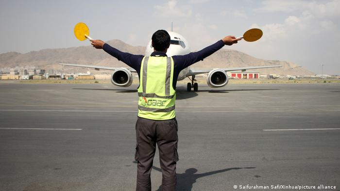 A member of the ground crew gives signals to the pilot of a plane at Kabul International Airport in Kabul, capital of Afghanistan