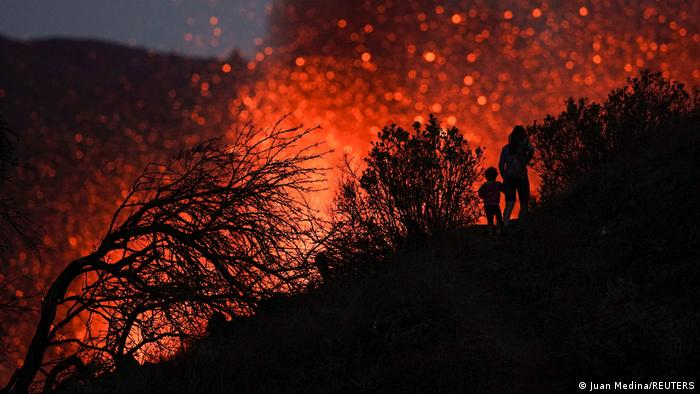 A woman climbs a hill with a child to see the Cumbre Vieja volcano as it continues to erupt in Tacande de Arriba on the Canary Island of La Palma, Spain.