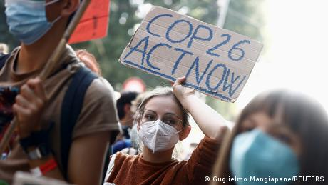 People take part in the 'Global march for climate justice' while environment ministers meet ahead of Glasgow's COP26 meeting, in Milan, Italy