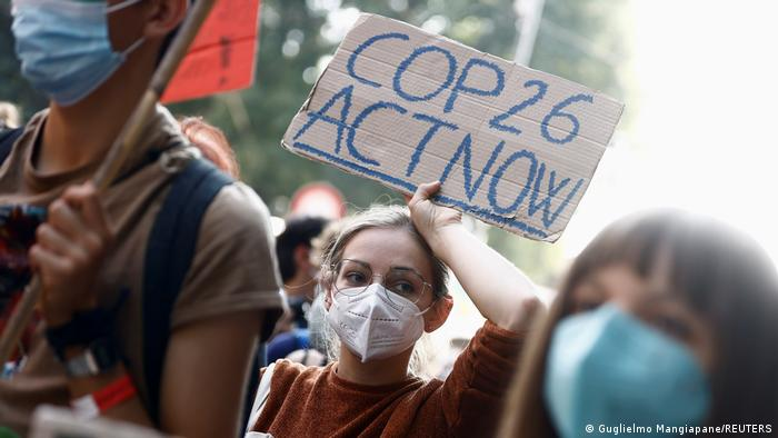 A person in a march for climate justice holding a banner that reads, COP26 ACT NOW