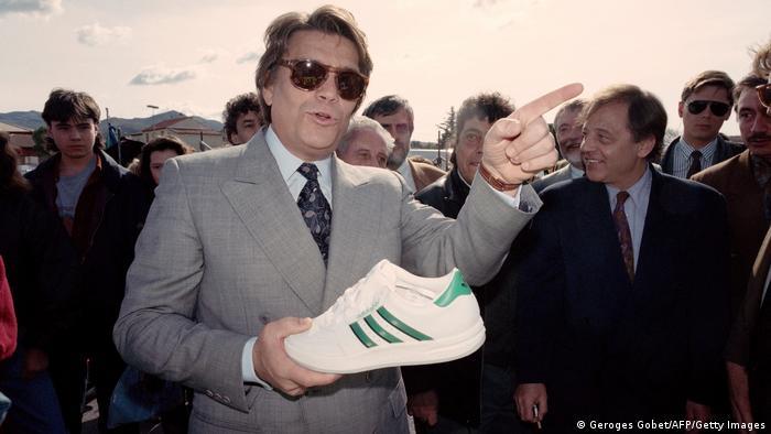 Bernard Tapie 1992 mit einem Schuh des Sportartikelherstellers Adidas, dessen Aktienmehrheit er zwei Jahre zuvor erworben hatte