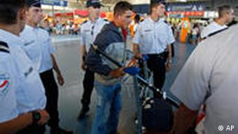 A Roma youth being escorted by police to the check-in desk at Roissy Charles de Gaulle airport near Paris