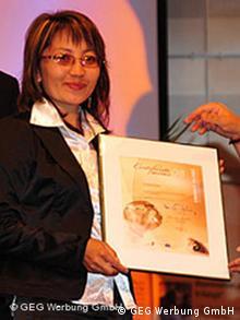 Frau wird mit Urkunde ausgezeichnet (Quelle: GEG)