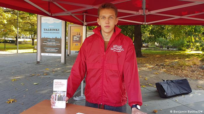Artjom Dmitrijev holding pamphlets at an outdoor campain stand.