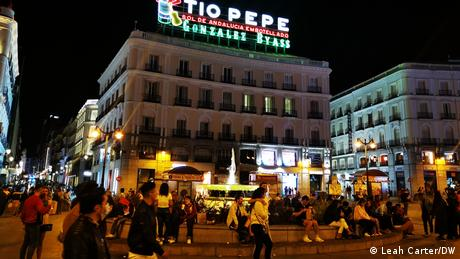 Public square in Madrid filled with people at night