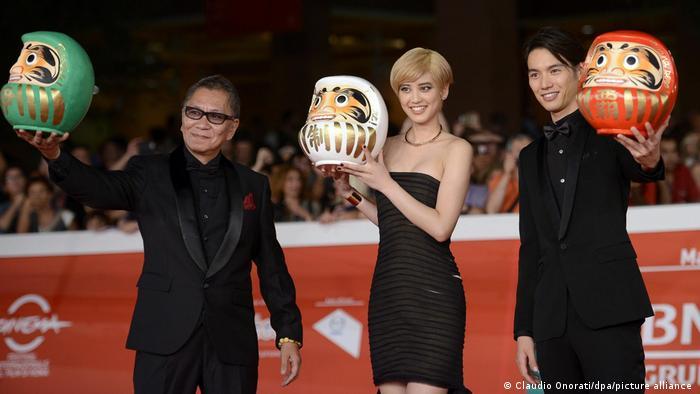 Japanese director Takashi Miike, and actors Hirona Yamazaki and Sota Fukushi show heads of Daruma dolls 'As the Gods Will'