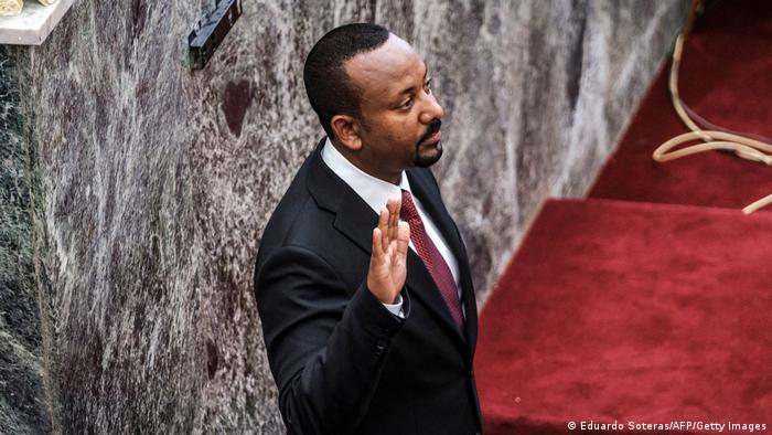 Abiy Ahmed holds up his hand as he is sworn in