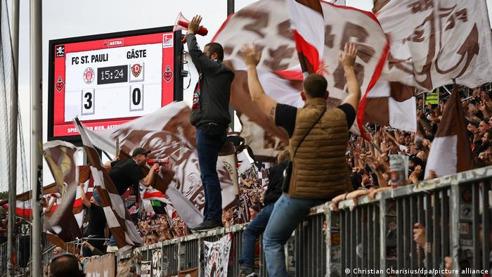 Fans of FC St. Pauli display banners and dance at a match against Dynamo Dresden