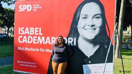 Isabel Cademartori vor einem Wahlplakat mit ihrem Foto.