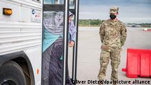 Eine afghanische Frau steigt aus einem Bus, um zur Impfung auf dem amerikanischen Stützpunkt in Ramstein zu gehen. Nach der Entdeckung einzelner Masern-Infektionen werden nun tausende geimpft. +++ dpa-Bildfunk +++