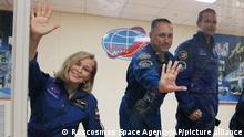 In this handout photo released by Roscosmos, actress Yulia Peresild, left, director Klim Shipenko, right, and cosmonaut Anton Shkaplerov, members of the prime crew of Soyuz MS-19 spaceship gesture after a news conference at the Russian launch facility in the Baikonur Cosmodrome, Kazakhstan, Monday, Oct. 4, 2021. In a historic first, Russia is set to launch an actress and a film director to space to make a feature film in orbit. Actress Yulia Peresild and director Klim Shipenko are set to blast off Tuesday for the International Space Station in a Russian Soyuz spacecraft together with Anton Shkaplerov, a veteran of three space missions.(Roscosmos Space Agency via AP)