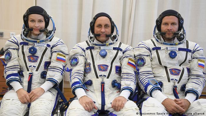 Um mulher e dois homens sentados, com roupas de cosmonautas.