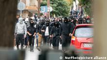 A crowd of students wearing black set up road blocks and march in the street against the police and journalists
