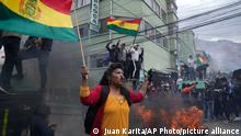 Anti-government coca farmers fly Bolivian flags during clashes with the police near the coca market in La Paz, Bolivia, Monday, Oct. 4, 2021. The anti-government coca farmers retook control of the coca market after more than two weeks of violent protests in a dispute for the leadership of their association. (AP Photo/Juan Karita)