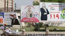 An Iraqi street vendor walks past an electoral billboards showing candidates for the upcoming parliamentary elections in the Karrada district of the capital Baghdad on September 29, 2021. - Iraqis cast ballots next month under a new electoral law that allows voting for independent candidates that was approved after an unprecedent protest movement led by youths fed up with the war-scarred country's old-style politics. (Photo by AHMAD AL-RUBAYE / AFP) (Photo by AHMAD AL-RUBAYE/AFP via Getty Images)