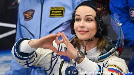 Schauspielerin Julia Peressild trägt einen Astronauten-Anzug und hält die Hände zu einem Herz geformt