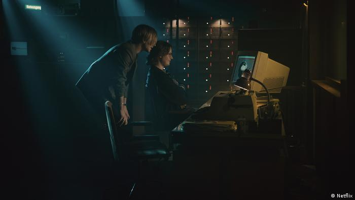 Film still from 'The Billion Dollar Code': two people in a dark room staring at a computer from the 1990s, one is sitting and the other one stands behind him.