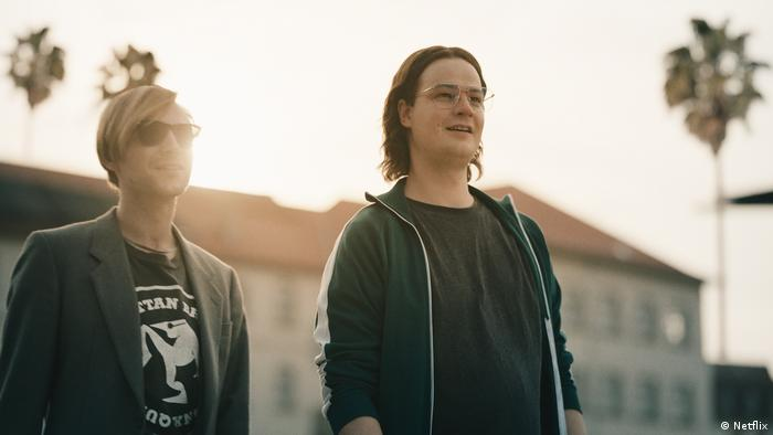 Film still from 'The Billion Dollar Code': two young men smile in a sunny urban setting, palm trees in the background.