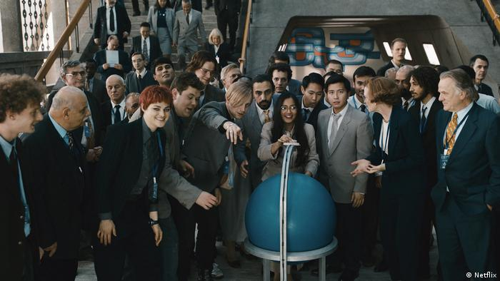 Film still from 'The Billion Dollar Code': a bunch of people wearing suits standing around a globe.