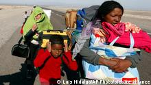 Migrants from Venezuela walk on the shoulder of a highway after crossing into Chile from the Bolivian border, near Colchane, Chile, Saturday, Feb. 6, 2021. (AP Photo/Luis Hidalgo)
