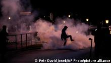 A demonstrator stomps on a smoke canister during a protest against vaccinations and coronavirus measures in Ljubljana, Slovenia, Tuesday, Oct. 5, 2021. EU leaders are meeting Tuesday evening in nearby Kranj, Slovenia, to discuss increasingly tense relations with China and the security implications of the chaotic U.S.-led exit from Afghanistan, before taking part in a summit with Balkans leaders on Wednesday. (AP Photo/Petr David Josek)