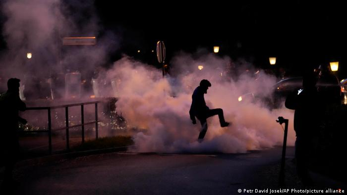 A demonstrator stomps on a smoke canister during a protest against vaccinations and coronavirus measures in Ljubljana, Sloveni