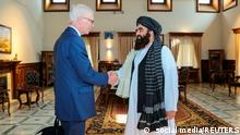 Simon Gass, Britain's Prime Minister Boris Johnson's high representative for Afghanistan, shakes hands with Taliban Acting Foreign Minister Amir Khan Muttaqi, in this picture uploaded on social media on October 5, 2021. Obtained from social media/via REUTERS THIS IMAGE HAS BEEN SUPPLIED BY A THIRD PARTY