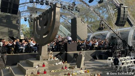 Babi Yar memorial ceremony, people assembled on a site with a statue in the shape of a menorah.