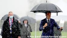 French President Emmanuel Macron, right, arrives in the rain for an EU summit at the Brdo Congress Center in Kranj, Slovenia, Wednesday, Oct. 6, 2021. European Union leaders are gathering Wednesday to reassure six countries in the Balkans region that they could join the trading bloc one day if they can meet its standards but are unlikely to give any signal even about when they might advance in their quests. (AP Photo/Petr David Josek)