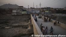 Afghans cross a bridge above the Kabul river in Kabul, Afghanistan, Tuesday, Sept. 28, 2021. (AP Photo/Felipe Dana)