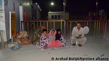 A family gather outside their house following a severe earthquake hit the area, in Quetta, Pakistan, Thursday, Pakistan. A powerful earthquake shook parts of southwestern Pakistan early Thursday.(AP Photo/Arshad Butt) 07.10.2021