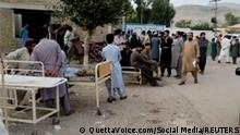People gather outside a hospital following an earthquake in Harnai, Balochistan, Pakistan, October 7, 2021, in this still image obtained from video. Courtesy of QuettaVoice.com / Social Media via REUTERS ATTENTION EDITORS - THIS IMAGE HAS BEEN SUPPLIED BY A THIRD PARTY. NO RESALES. NO ARCHIVE. MANDATORY CREDIT QUETTAVOICE.COM.