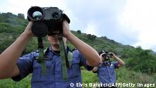 TO GO WITH AFP STORY BY LAJLA VESELICA Croatian border police officers use thermo-sensitive binoculars to observe surroundings while on foot patrol along the border between Croatia and Montenegro, close to the Croatian village of Karasovici on June 5, 2013. Croatian border is expected to become the most Southern border of the EU after the country joins the bloc on July 1, 2013. Croatia is gearing up to lavishly celebrate joining the European Union on July 1, but economic worries are overshadowing the festivities planned to mark the successful end of the Balkan country's 10-year bid for membership. AFP PHOTO ELVIS BARUKCIC (Photo credit should read ELVIS BARUKCIC/AFP via Getty Images)