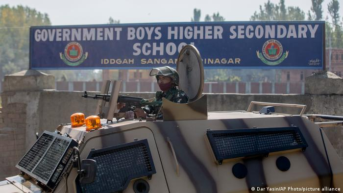 An Indian parailitary soldier stands guard in a tank