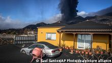 Ash covers a house, car and garden as in the background a volcano erupts on the Canary island of La Palma, Spain on Monday Oct. 4, 2021. More earthquakes are rattling the Spanish island of La Palma, as the lava flow from an erupting volcano surged after part of the crater collapsed. Officials say they don't expect to evacuate any more people from the area, because the fiery molten rock was following the same route to the sea as earlier flows. (AP Photo/Saul Santos)