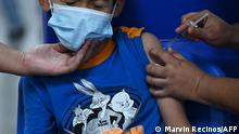 (FILES) In this file photo taken on September 22, 2021 a child receives a dose of the Sinopharm Covid-19 vaccine at El Salvador's main vaccination center in San Salvador. - The Argentine government announced on October 1st the approval of the use of the Chinese Sinopharm vaccine to immunise children aged 3 to 11 against covid-19, the only age group that has not yet begun the immunisation process in the South American country. (Photo by MARVIN RECINOS / AFP)