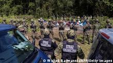 Polish border guards (foreground) stand next to migrants believed to be from Afghanistan in the small village of Usnarz Gorny near Bialystok, northeastern Poland, located close to the border with Belarus, on August 20, 2021. - The fate of a group of 32 bedraggled migrants stranded at a makeshift encampment on the border between Belarus and Poland for nearly two weeks has sparked a heated debate in Poland. The sight of the migrants, who are believed to be from Afghanistan, stuck between armed Belarusian officers and Polish soldiers just a few metres away has moved many Poles. (Photo by Wojtek RADWANSKI / AFP) (Photo by WOJTEK RADWANSKI/AFP via Getty Images)