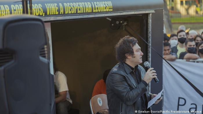 Javier Milei: Man with microphone stands on a stage, crowds in background