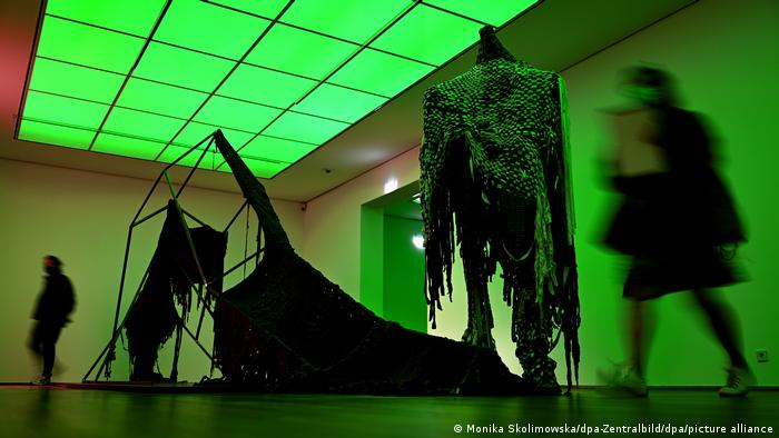 Greenly lit room in a museum with exhibits and two people