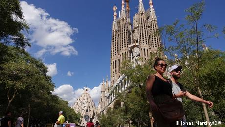 People walking with the Sagrada Familia in the background