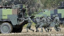 (FILES) In this file photo taken on January 17, 2017 Taiwan special forces personnel walk behind an armoured personnel carrier during an annual military drill in Taichung, central Taiwan. - US special operations forces and marines have been secretly training Taiwanese troops for more than one year, risking the ire of China, the Wall Street Journal reported on October 7, 2021. (Photo by SAM YEH / AFP)