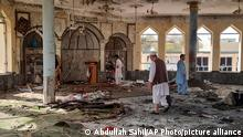 People inspect the inside of a mosque following a bombing in Kunduz province northern Afghanistan, Friday, Oct. 8, 2021. A powerful explosion in the mosque frequented by a Muslim religious minority in northern Afghanistan on Friday has left several casualties, witnesses and the Taliban's spokesman said. (AP Photo/Abdullah Sahil)