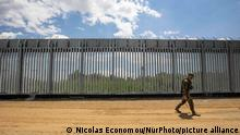 An armed military personnel is patroling along the fence, while there is a Turkish watchtower in the background behind the new fence. Greece is reinforcing the Greek Turkish borders with personnel, cameras, drones, heavy vehicles, FRONTEX officers but also with a 5 meter tall fence. The fence is actually a concrete filled, a construction for at least 40KM, a long coverage in the wetlands of Evros river (Meric in Turkish), Greece's river border with Turkey. EU is supporting the border fortification financially. Asylum seekers, migrants and refugees used Evros as an entrance point to Europe, while in March 2020 a huge wave of thousands of people tried to cross the borders. Poros Village, Evros region, Greece on June 18, 2021 (Photo by Nicolas Economou/NurPhoto)