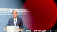 In this photo taken with a television camera control light in the foreground, Christian Democratic Union party chairman Armin Laschet speaks to media at the party's headquarters in Berlin, Thursday, Oct. 7, 2021. (AP Photo/Markus Schreiber)
