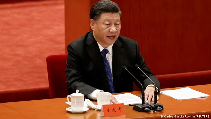 Xi Jinping wears a balck suit and blue tie as he sits at a brown wooden long table. There are some tea cups near his right hand and a speech in front of him.