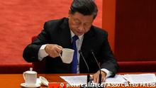Chinese President Xi Jinping drinks as he delivers a speech at an event commemorating the 110th anniversary of Xinhai Revolution at the Great Hall of the People in Beijing, Saturday, Oct. 9, 2021. Xi said on Saturday reunification with Taiwan must happen and will happen peacefully, despite a ratcheting-up of China's threats to attack the island. (AP Photo/Andy Wong)