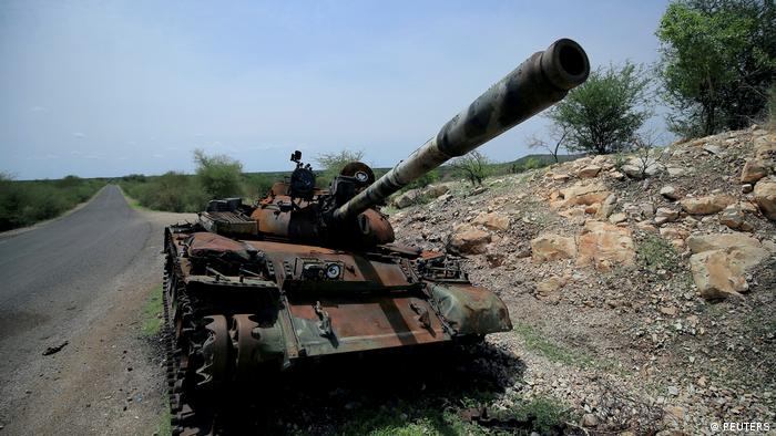 A tank damaged during fighting between Ethiopian federal forces and Tigray forces stands on the side of the road
