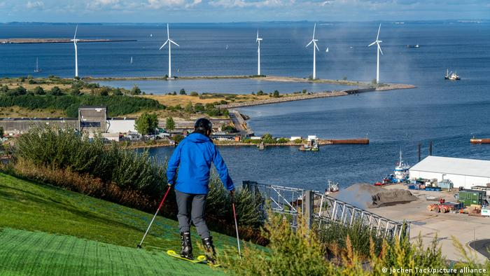 a person in a blue coat skis on a slope while looking out at the sea with some wind turbines near the coast