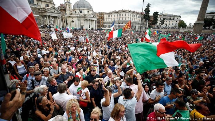 Foto de personas que protestan contra el pasaporte sanitario en Italia.